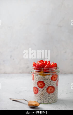 healthy breakfast. overnight oatmeal with strawberries, chia seeds in a glass jar on a gray background - Stock Photo
