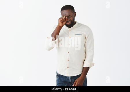 Studio shot of good-looking timid and insecure adult African American man with beard in white shirt, giving up, crying, whiping tears with fist on closed eyes, whining, having bad day over grey wall - Stock Photo