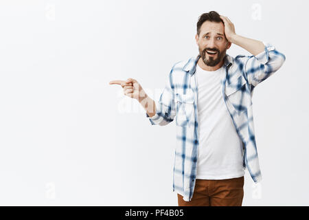 His car broke down, guy asking stranger take him to gas station. Portrait of upset helpless handsome man with beards, pointing left with index finger and holding palm on head, being in tough situation - Stock Photo