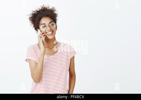 Close-up shot of confident pleased good-looking woman in glasses and striped t-shirt, smiling broadly and gazing right while talking on brand new smartphone, discussing future party over gray wall - Stock Photo