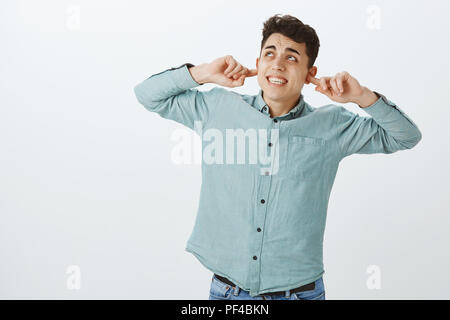 Portrait of bothered fed up boyfriend, covering ears with index fingers and looking up with frowned eyebrows and clenched teeth, being annoyed with loud repairing works in neighbors apartment - Stock Photo