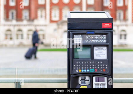 Car park ticket machine on a London street with an unidentified traveller in the background - Stock Photo