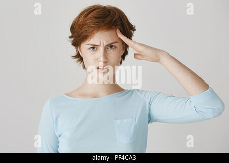 Girl prepares for her duties seriously. Portrait of focused and confident redhead woman with freckles, frowning, being serious while saluting captain or greeting soldier, standing over gray wall - Stock Photo