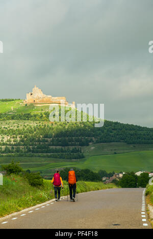 Pilgrims men and women approaching the Spanish  town of Castrojeriz with its Templar Castle while walking the Camino de Santiago pilgrimage route - Stock Photo