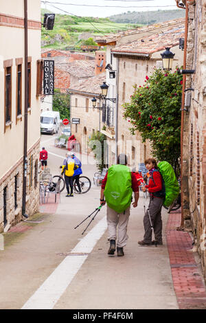 Pilgrims approaching the village of Hontanas while  walking on the way of St James the Camino de Santiago Burgos Castille y Leon Spain - Stock Photo