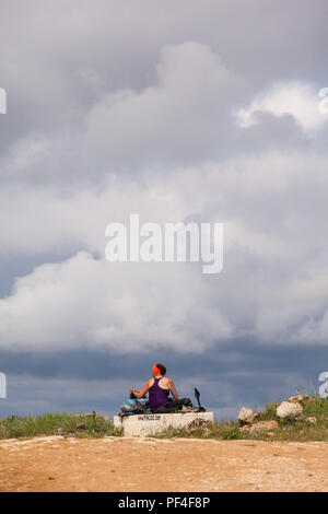 Woman pilgrim taking a rest while walking alone on the Camino de Santiago the way of St James near the village of Hontanas Burgos Spain - Stock Photo