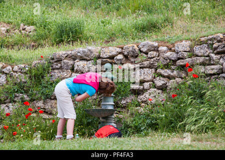 Woman pilgrim drinking water  from a fountain in the village of Hontanas while walking the way of St James the Camino de Santiago Burgos - Stock Photo