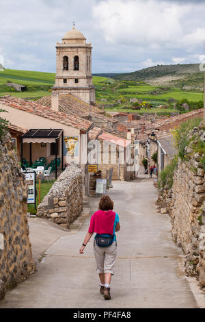 Pilgrim woman approaching the village of Hontanas while  walking on the way of St James the Camino de Santiago Burgos Castille y Leon Spain - Stock Photo