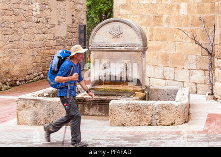 Man pilgrim walking alone past the water fountain in the village of Hontanas on the way of St James the Camino de Santiago Burgos Castille y Leon - Stock Photo