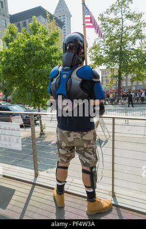 Seattle, WA, USA.  18th August, 2018.  A pro gun supporter in a protective gear  holdig an American flag look towards counterprotesters yelling on the other side of street. at the pro gun rally at the City Hall Plaza.  Credit: Maria S./Alamy Live News. - Stock Photo