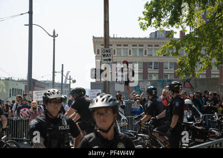 Seattle, WA, USA.  18th August, 2018.  A female  anti gun supporter stand  on a pedestal looking at th pro gun supporters marching down the street .Credit: Maria S./Alamy Live News. - Stock Photo