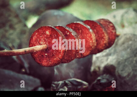 Making and cooking Hot dog smoked sausages over open camp fire. Grilling food over flames of bonfire on wooden branch - stick spears in nature. Scouts - Stock Photo