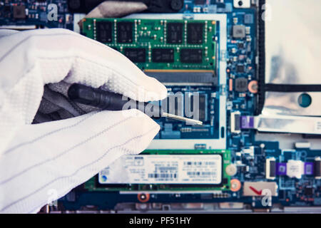 Replacement of memory in the laptop, in one of the service centers for repair of laptops. hand in a white glove holds a screwdriver on the background  - Stock Photo