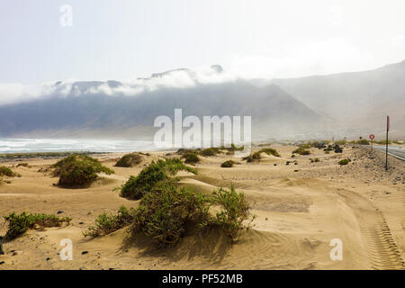 Caleta de Famara landscape with desert dunes and mist on mountains on the background, Lanzarote, Canary Islands - Stock Photo