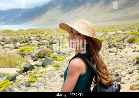 Happy beautiful traveler girl with straw hat looking to the camera. Young female backpacker exploring Lanzarote, Canary Islands. - Stock Photo