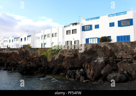 Typical canarian white houses in Punta Mujeres on sea rocks, Lanzarote Island - Stock Photo