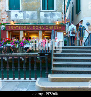 Venice, Italy - June 18, 2018: People at small restaurant with tables outdoors near small canal in Venice - Stock Photo