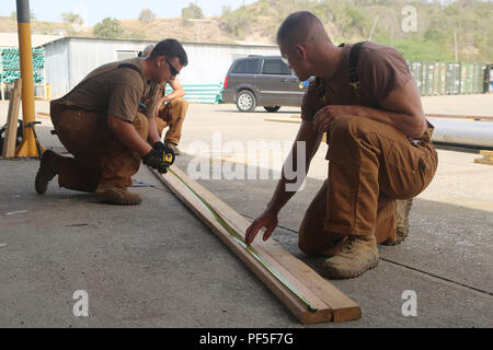 U.S. Navy Builder 3rd Class Zachary Pavia (left) and Construction Mechanic 2nd Class Brady Mangels, assigned to Naval Mobile Construction Battalion (NMCB) 133, take a measurement  aboard Naval Base Guantanamo Bay, Cuba, Aug. 9, 2018, in support of Southern Partnership Station 2018. Southern Partnership Station is a U.S. Southern Command-sponsored and U.S.  Naval Forces Southern Command/U.S. 4th Fleet-conducted annual deployment focused on subject matter expert exchanges and building partner capacity in a variety of disciplines  including medicine, construction and dive operations in the Caribb - Stock Photo