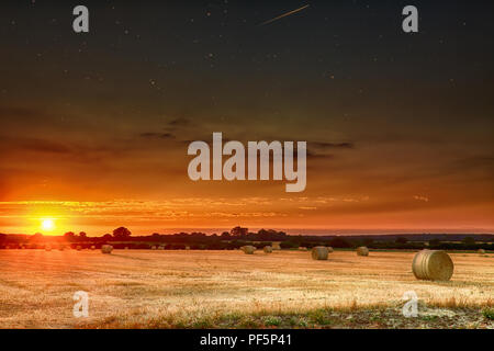 Hay bales at sunset with skies clearing to show stars at night. Beautiful panoramic evening orange sun over rural crop fields in Norfolk - Stock Photo