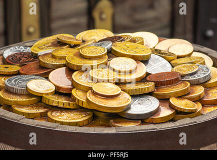 A lot of gold coins on a wooden barrel - Stock Photo