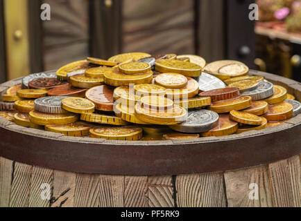 A lot of gold coins on a wooden barrel, the concept of wealth - Stock Photo