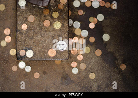 Coins on the ground/wall for good fortune out of superstition - Stock Photo