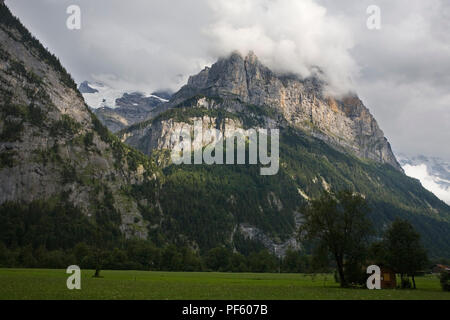 Trümmelbach Gorge (aka Trümmeltal) with the Schwarzmönch beyond and the flat floor of the Lauterbrunnen Valley in front, Bernese Oberland, Switzerland - Stock Photo