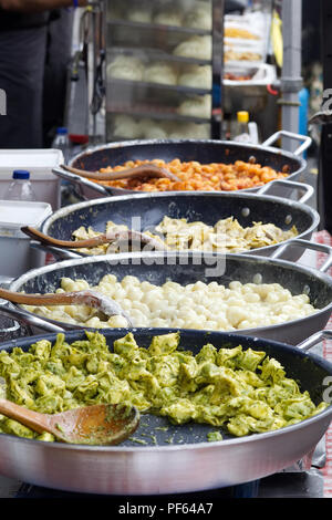 pasta dishes cooking on a market stall. - Stock Photo