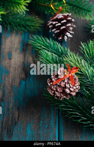 Fir branches with cones on wooden rustic desk. Christmas decoration. - Stock Photo