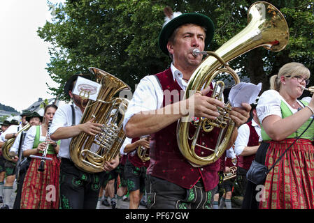 Usseln, Germany - July 30th, 2018 - Bavarian marching band in traditional dress playing brass instruments at a parade - Stock Photo