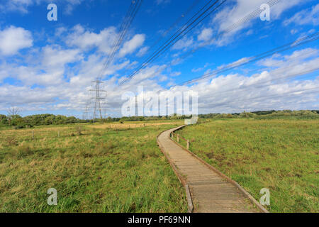 Electricity pylons and boardwalk through the tidal Lower Test Marshes, a nature reserve between Totton and Redbridge, Southampton, Hampshire, UK - Stock Photo