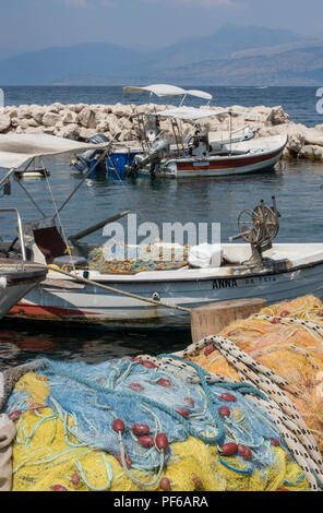 fishing boats and fishing nets at kassiopi harbour on the north east coast of corfu , greece. - Stock Photo