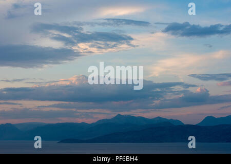 atmospheric sunset over the mountains on the Albanian coast with beautiful colours in the sky. - Stock Photo