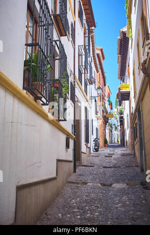 Walking up a narrow empty cobbled traditional street in Granada, Andalucia, Spain in the daytime - Stock Photo