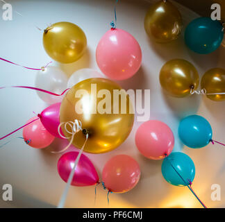 A bunch of balloons from a celebration are filled with helium and float to the ceiling - Stock Photo