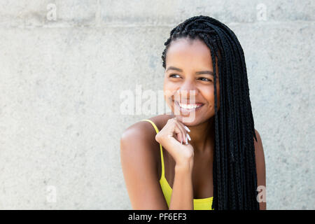 Beautiful african ameircan woman with dreadlocks looking sideways outdoors in the summer - Stock Photo