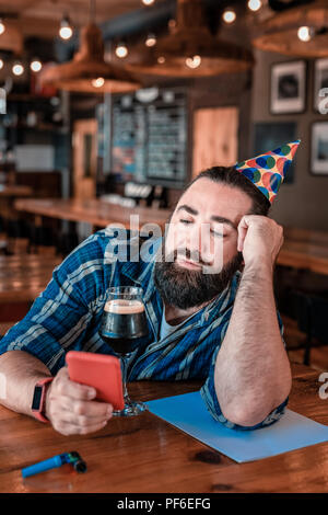 Bearded dark-haired man waiting for his friends in the bar - Stock Photo