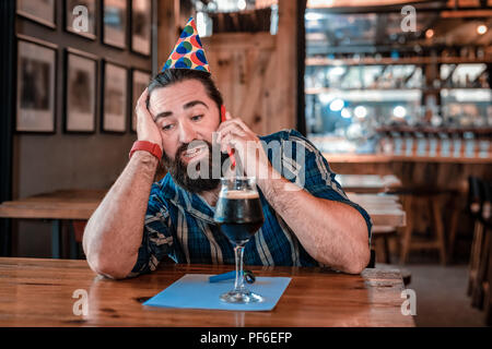 Man calling his friends waiting for them in pub on his birthday - Stock Photo