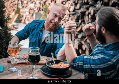 Bearded men arm wrestling while drinking beer together - Stock Photo