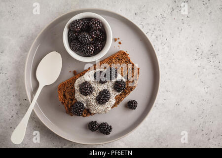 Chocolate vegan banana bread with chia pudding and blackberries, white background. Clean eating concept. - Stock Photo