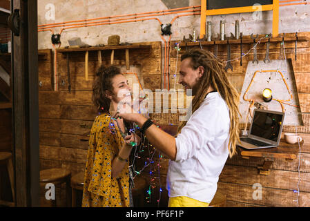 Two flower children having fun while decorating building - Stock Photo
