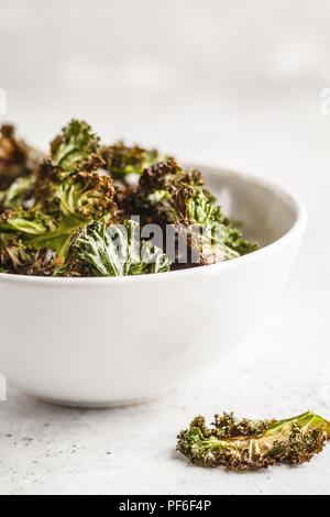 Kale chips in a white bowl on white background. Clean eating concept. Go vegan! - Stock Photo
