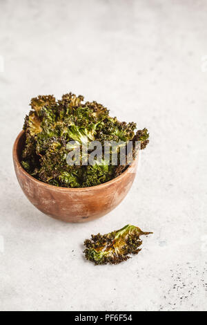 Kale chips in a wooden bowl on white background. Clean eating concept. Go vegan! - Stock Photo