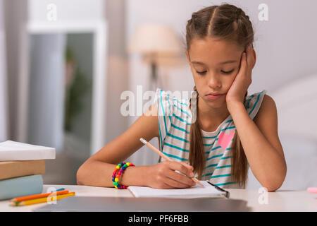 Sad school girl doing her hometask at home - Stock Photo