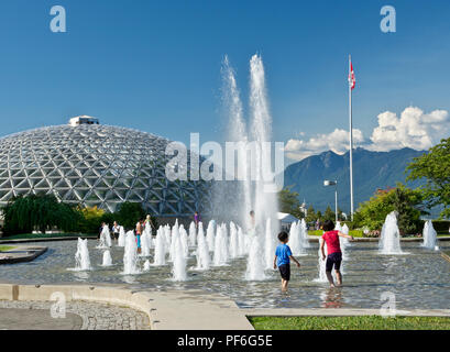 Queen Elizabeth Park in Vancouver, BC Canada.  Children playing in the fountain on a hot summer day. - Stock Photo