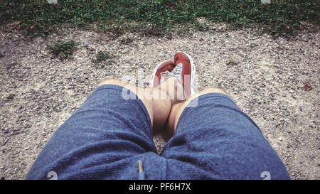 The legs of a sitting man in shorts and sneakers. View from above. - Stock Photo