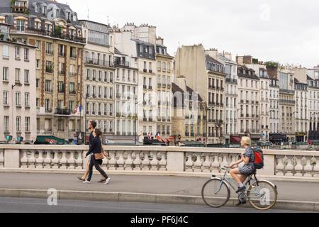 Paris cityscape - Woman cycling over the Saint Michel bridge, buildings on Quai des Grands Augustins are in the background. Paris, France, Europe. - Stock Photo