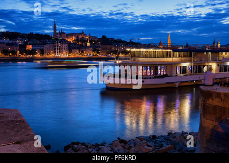 Danube River at blue hour twilight in city of Budapest, Hungary, cruise and dinner boat, view from Pest to Buda side. - Stock Photo