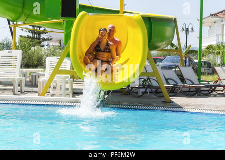 Happy Father and Daughter Sliding Down Water Slide - Stock Photo