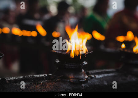 Oil lamps burning together in a row  in the temple of kathmandu Nepal. - Stock Photo